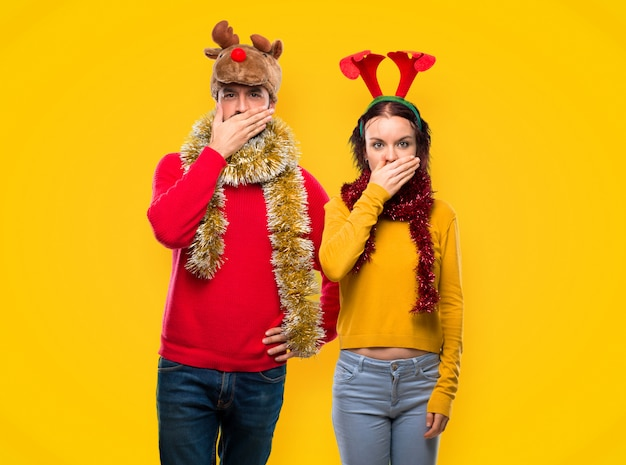 Couple dressed up for the christmas holidays covering mouth with hands for saying somethin