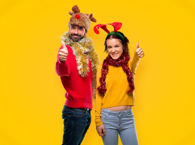 Couple dressed up for the christmas holidays giving a thumbs up gesture and smiling