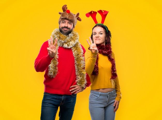 Couple dressed up for the christmas holidays happy and counting three with fingers