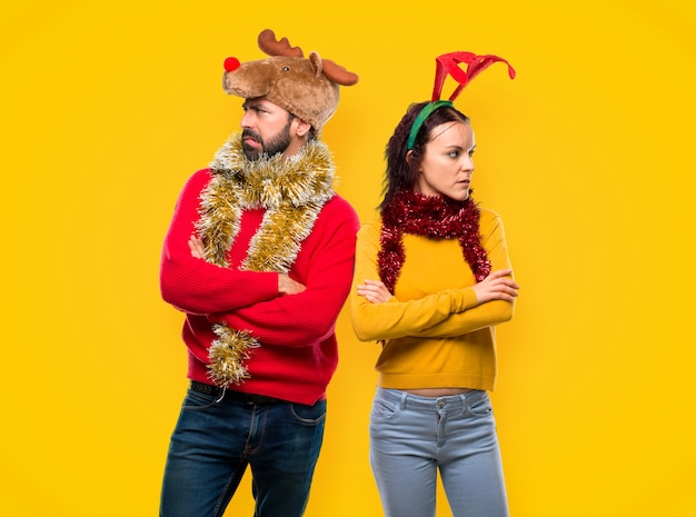 Couple dressed up for the christmas holidays having doubts and with confuse face expressio