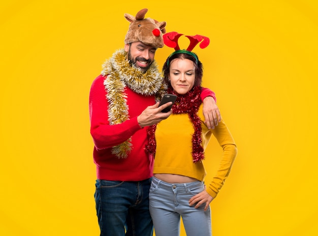 Couple dressed up for the christmas holidays holding a mobile on yellow background