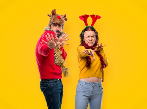 Couple dressed up for the christmas holidays is a little bit nervous and scared stretching