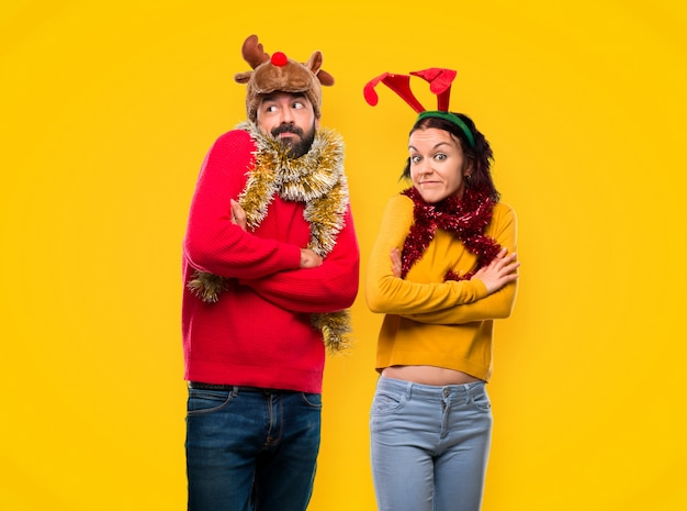 Couple dressed up for the christmas holidays making unimportant gesture while lifting the