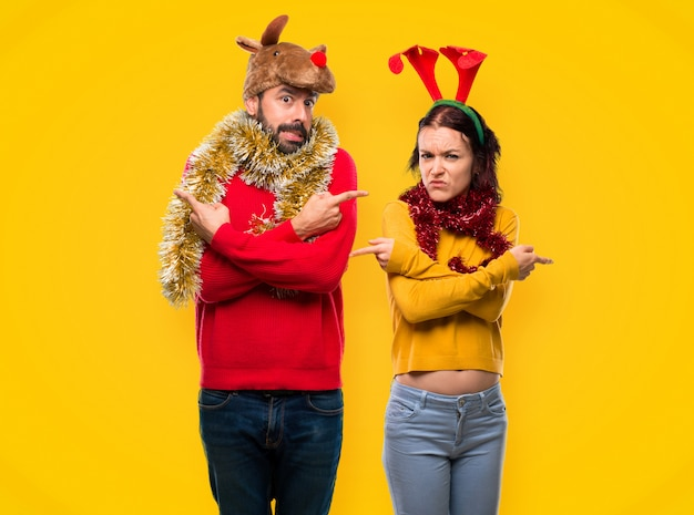 Couple dressed up for the christmas holidays pointing to the laterals having doubts