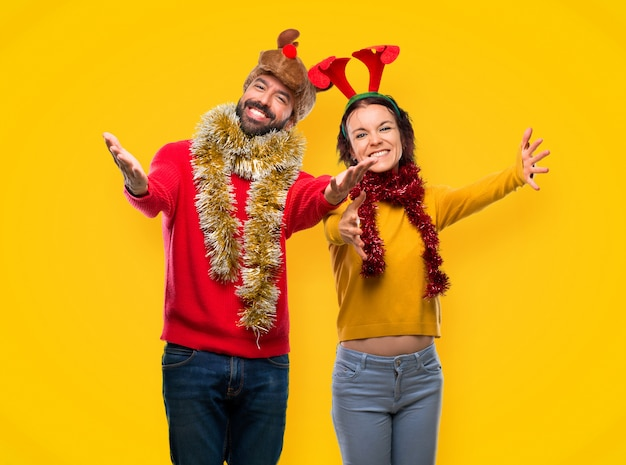Couple dressed up for the christmas holidays presenting and inviting to come