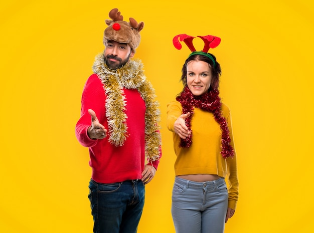 Couple dressed up for the christmas holidays shaking hands for closing a good deal