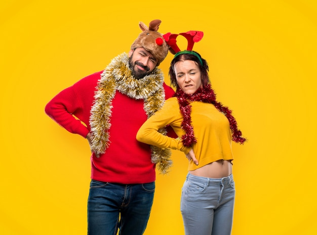 Couple dressed up for the christmas holidays suffering from backache for having made an ef