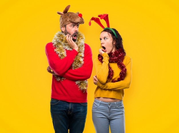 Couple dressed up for the christmas holidays surprised and shocked while looking right