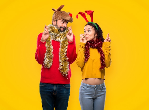 Couple dressed up for the christmas holidays with fingers crossing and wishing the best