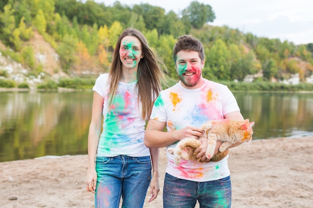 Couple dressed in white shirts holding cat and