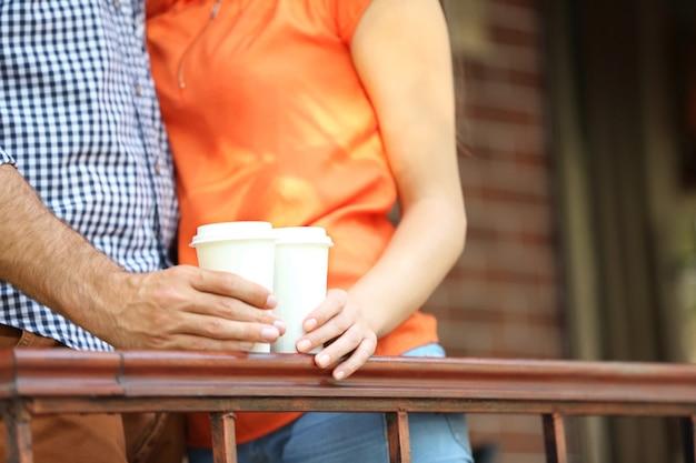カップルは屋外のカフェのクローズアップでコーヒーを飲みます