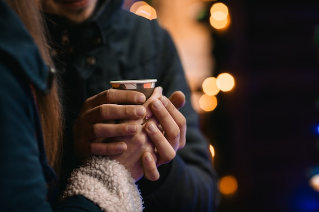 Couple drink coffee at the new year fair