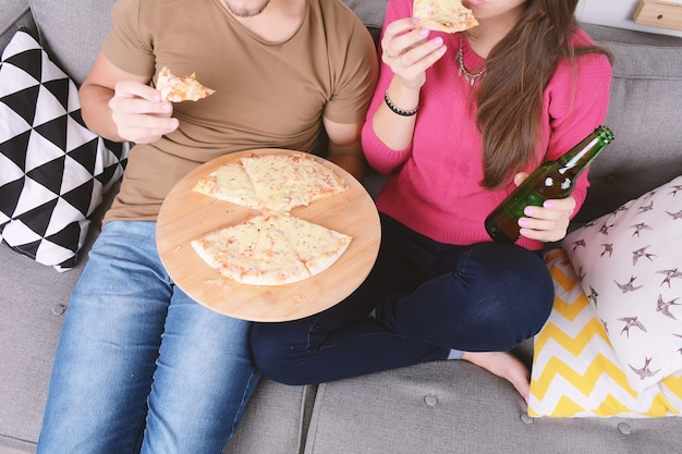 Couple drinking beer and eating pizza.