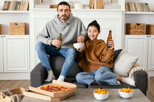 Couple drinking beer and eating snacks indoors
