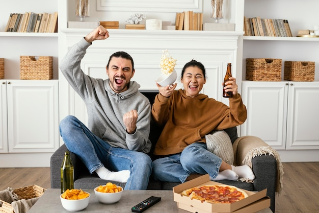 Couple drinking beer and eating snacks