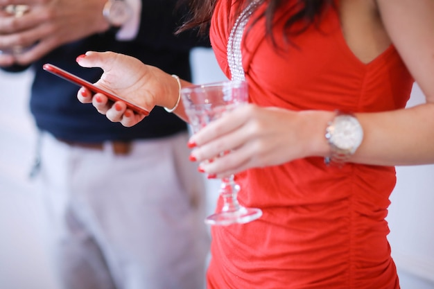 シャンパンを飲むとスマートフォンを探しているカップル
