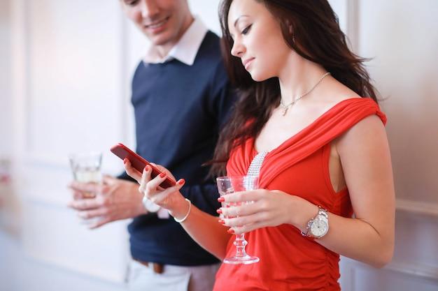 Пара пьет шампанское и смотрит на смартфон