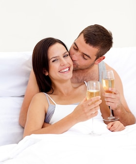Couple drinking champagne in bed in valentines day