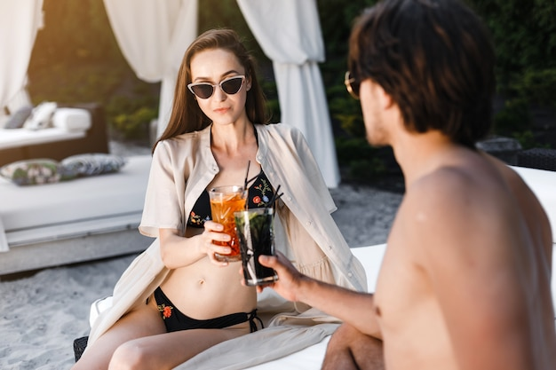 Couple drinking cocktail on beach
