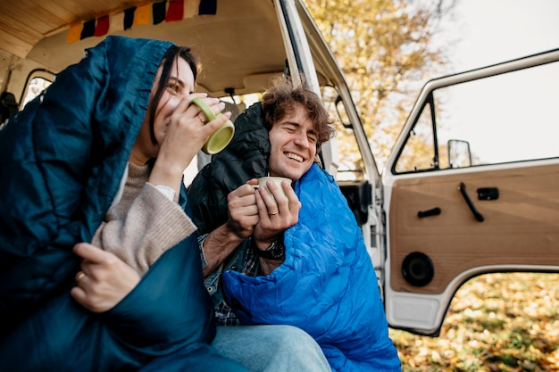 Couple drinking coffee from their van