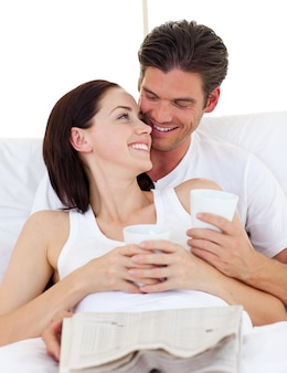 Couple drinking coffee and reading newspaper