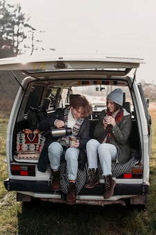 Couple drinking coffee in a van