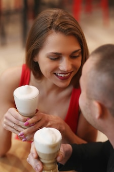 Coppie che bevono caffè con panna montata
