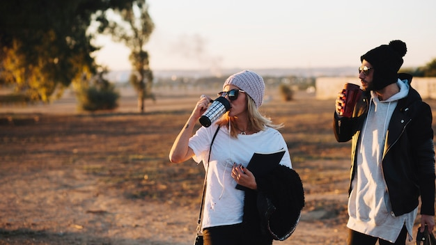 Couple drinking during walk in countryside