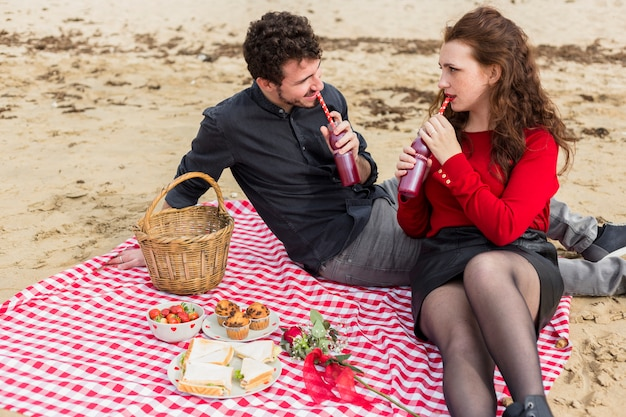Couple drinking from bottles on checkered coverlet