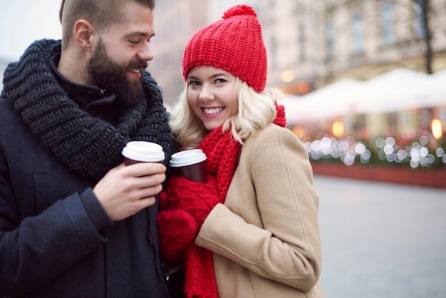屋外でホットコーヒーを飲むカップル