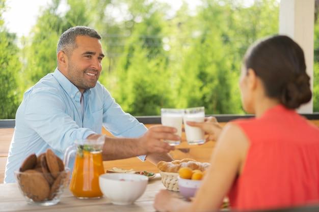 ミルクを飲むカップル。週末に外で朝食を楽しみながらミルクを飲むカップル