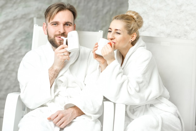 소금 방에 앉아 미네랄 워터를 마시는 커플. 스파에서 소금 요법 적용하기