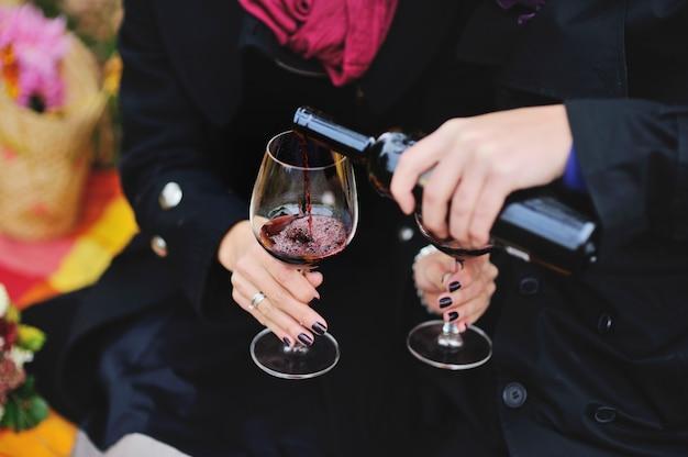 外のピクニックに赤ワインを飲むカップル