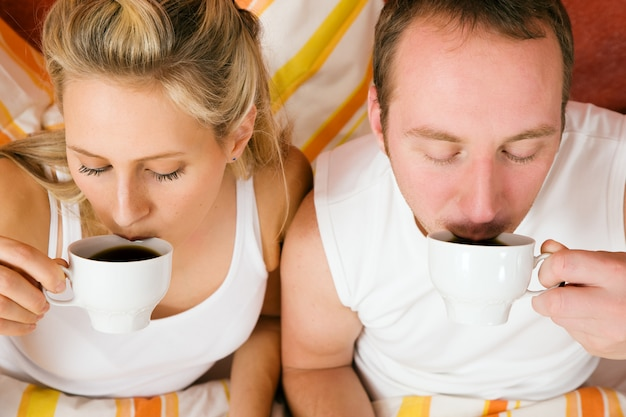 Couple drinking some coffee in the bead in morning