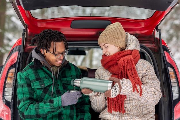 자동차 트렁크에 앉아있는 동안 차를 마시는 커플