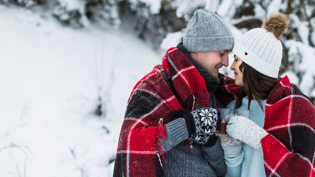 Couple drinking tea in winter forest