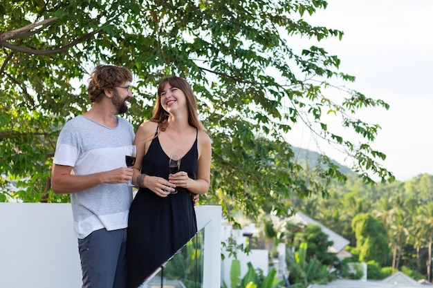 Couple drinking wine on balcony with topical palm trees view.