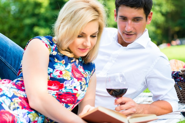 Couple drinking wine reading book on meadow having picnic