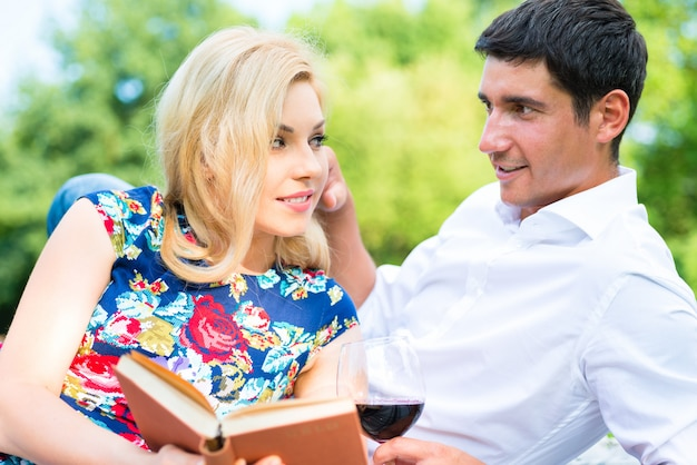 Couple drinking wine reading book on meadow