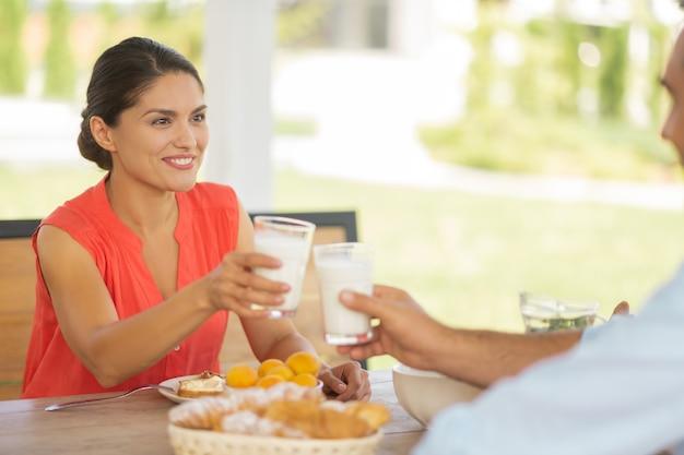 ヨーグルトを飲むカップル。一緒に外で朝食をとりながら、朝にヨーグルトを飲むカップル