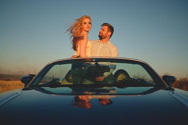 カブリオレの車で運転するカップル
