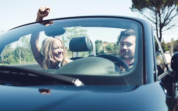 부부는 컨버터블 자동차를 운전하고 재미