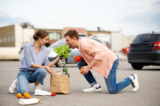 カップルがスーパーマーケットの駐車場に荷物を落とした