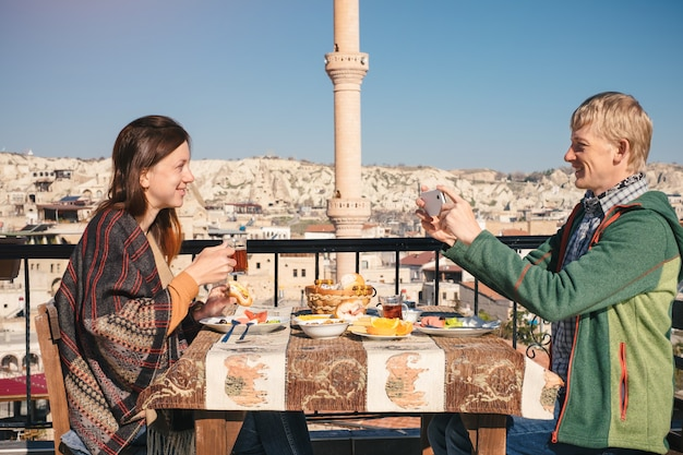 Couple eat traditional turkish breakfast on rooftop with city view