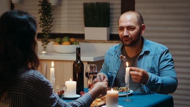 부엌에서 축제 저녁 식사를 하는 동안 전경에서 남자와 와인을 먹고 마시는 커플. 테이블 식당에 앉아 행복한 이야기를 하고, 집에서 촛불을 켜며 낭만적인 시간을 보내며 식사를 즐깁니다.