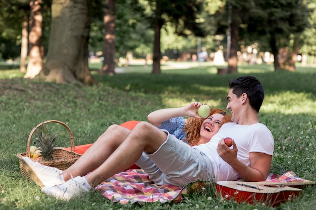 Couple eating apples together in the park