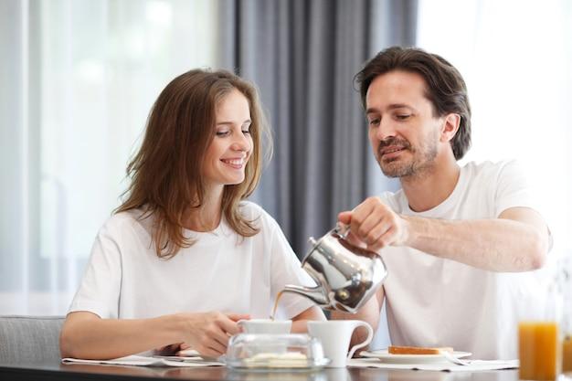 Пара завтракает на кухне
