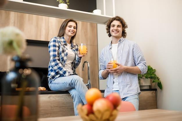 Coppia che fa colazione al mattino presto in cucina e si diverte con succo di frutta fresco.