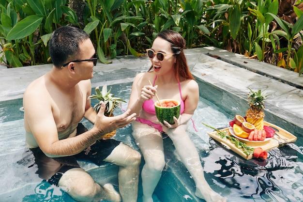 スイミングプールで朝食を食べるカップル