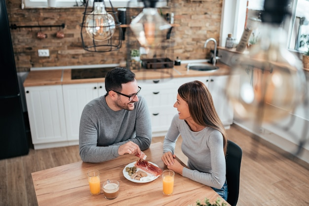 Couple eating breakfast at modern kitchen, high angle image.